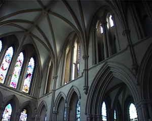 The outside of the aisle is divided from the nave with a wall with pointed arches cutting out entries. The ambulatory's walls have stained glass windows in the shape of pointed arches.