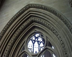 The pointed arch is framed with several layers of carving, all in the same pointed arch shape. The first and last layer have an intricate pattern carved into them.