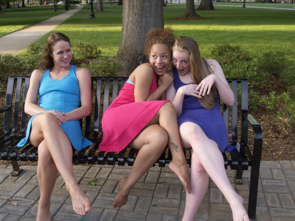Photo of three young women in bright dresses and bare feet sitting on a bench
