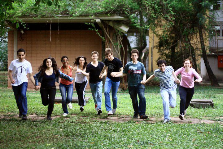 Nine young adults running outdoors towards the camera