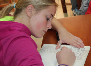 Photo of a young woman writing in a notebook