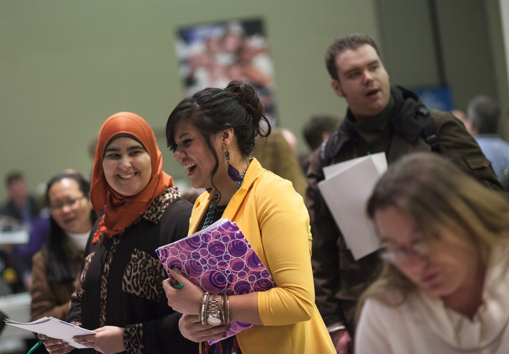 Photo of room full of active people. Central are two women, one wearing a head scarf, holding notebooks and laughing.
