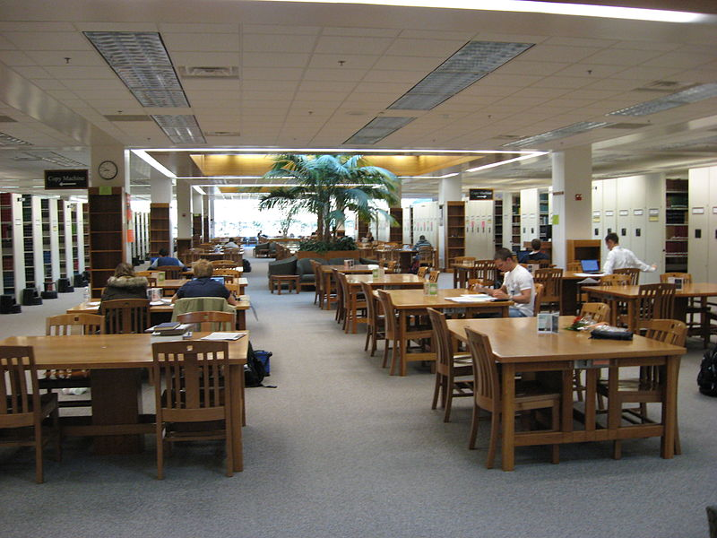 A college library where students are studying at tables.