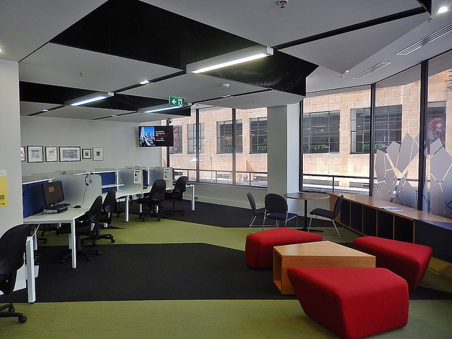 Photo of a modern workspace, with curved computer desks along one wall, movable red cushions and tables, and wide windows