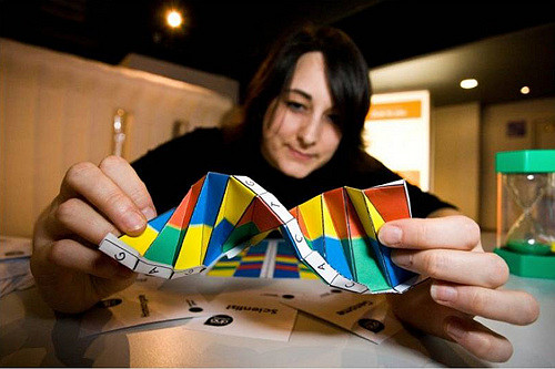 "Photo of a young woman holding brightly colored, twisted paper up to the camera, ""DNA Oragami"""