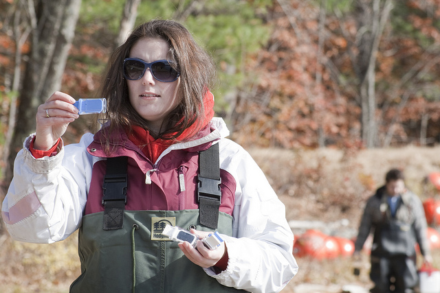 Photo of a young woman in waders, outdoors, looking at a water test strip