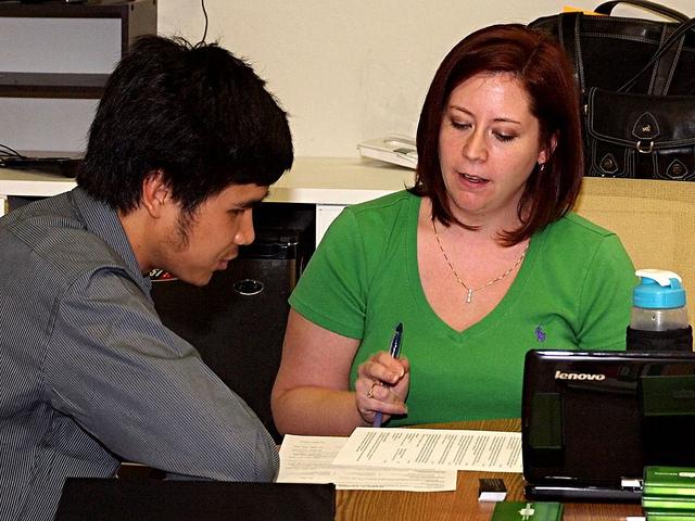 A counselor going over a résumé with a student.