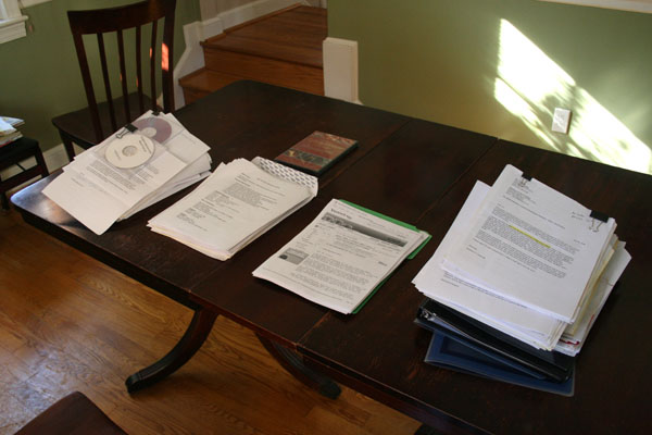 Table with four piles of papers waiting to be assembled into application packets