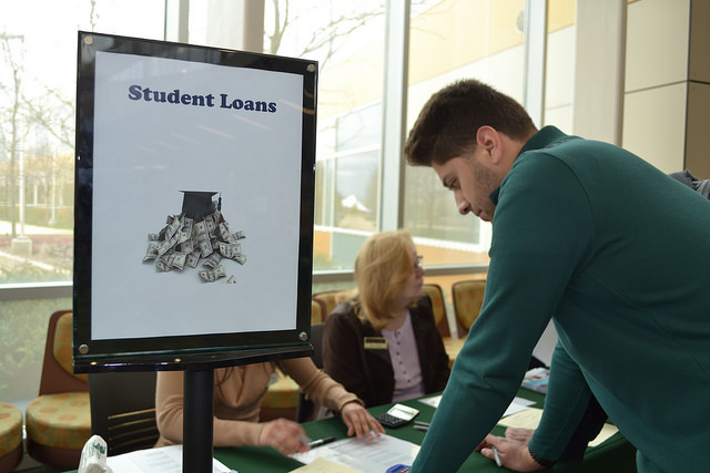 "A male student leans over a table with a sign on it that reads, ""Student Loans."" Two women are seated behind the table."