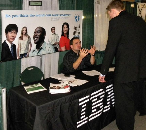 Man sitting at a career fair booth for IBM, gesturing to a student in a suit standing in front of him