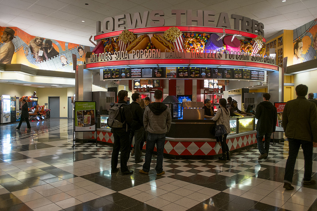 Photo of people standing in line at a concession stand in a Loews Theatre