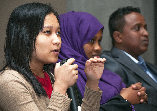 Photo of three people from ethnically diverse backgrounds sitting in a row. The woman closest to the camera holds a microphone, a woman in a burka sits next to her, and a man in a suit is at the end.