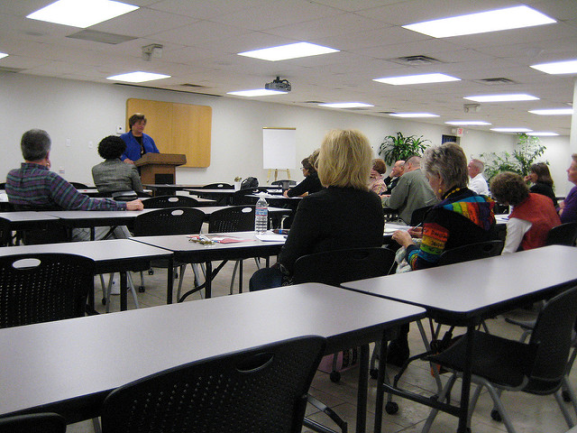 Photo of a woman at a lectern standing in front of a classroom of adults