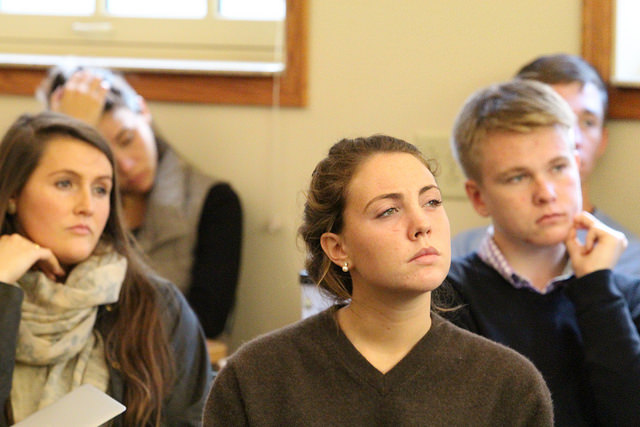 Photo of five students seated in class. All look deep in thought.