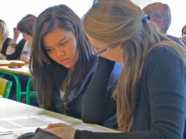 Photo of two young women reading the same sheet of paper on a desk, in a crowded classroom