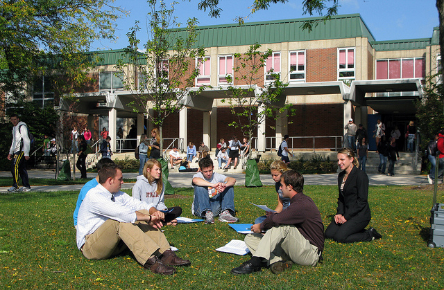 Photo of a group of students sitting in a circle on a lawn outside of a campus building, while other students stream around them