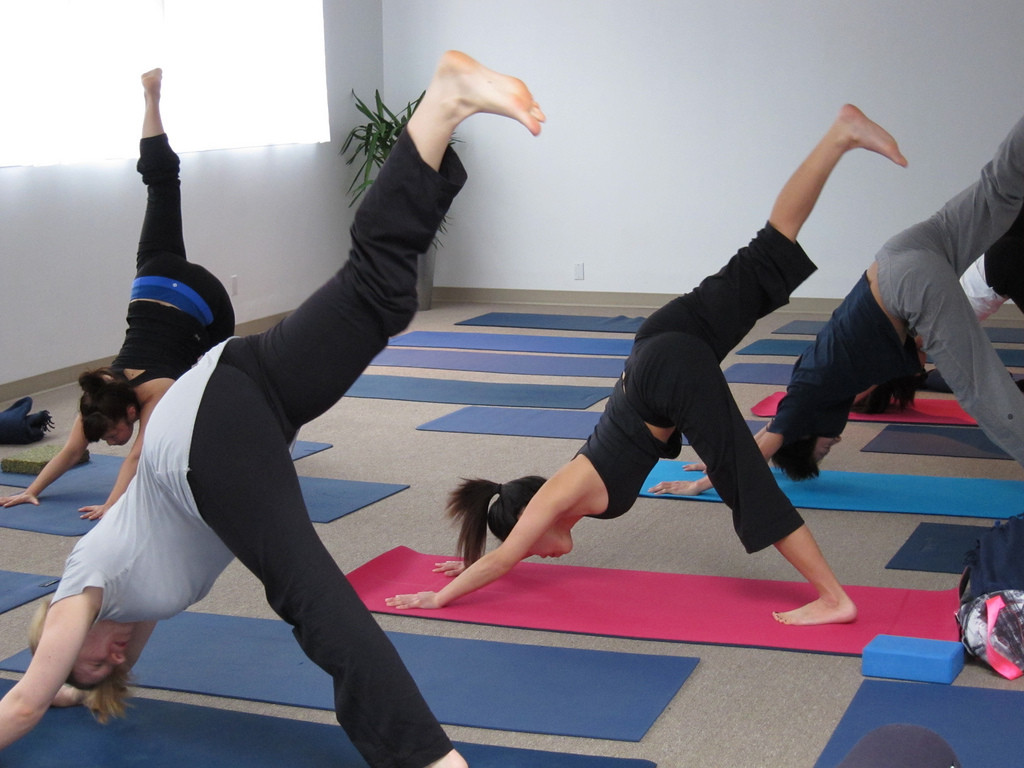 Five people in a yoga studio doing a yoga pose called three-legged dog: both hands are on the mat, head is down, one foot on the floor about a yard behind the hands, the other foot is extended straight up in the air.