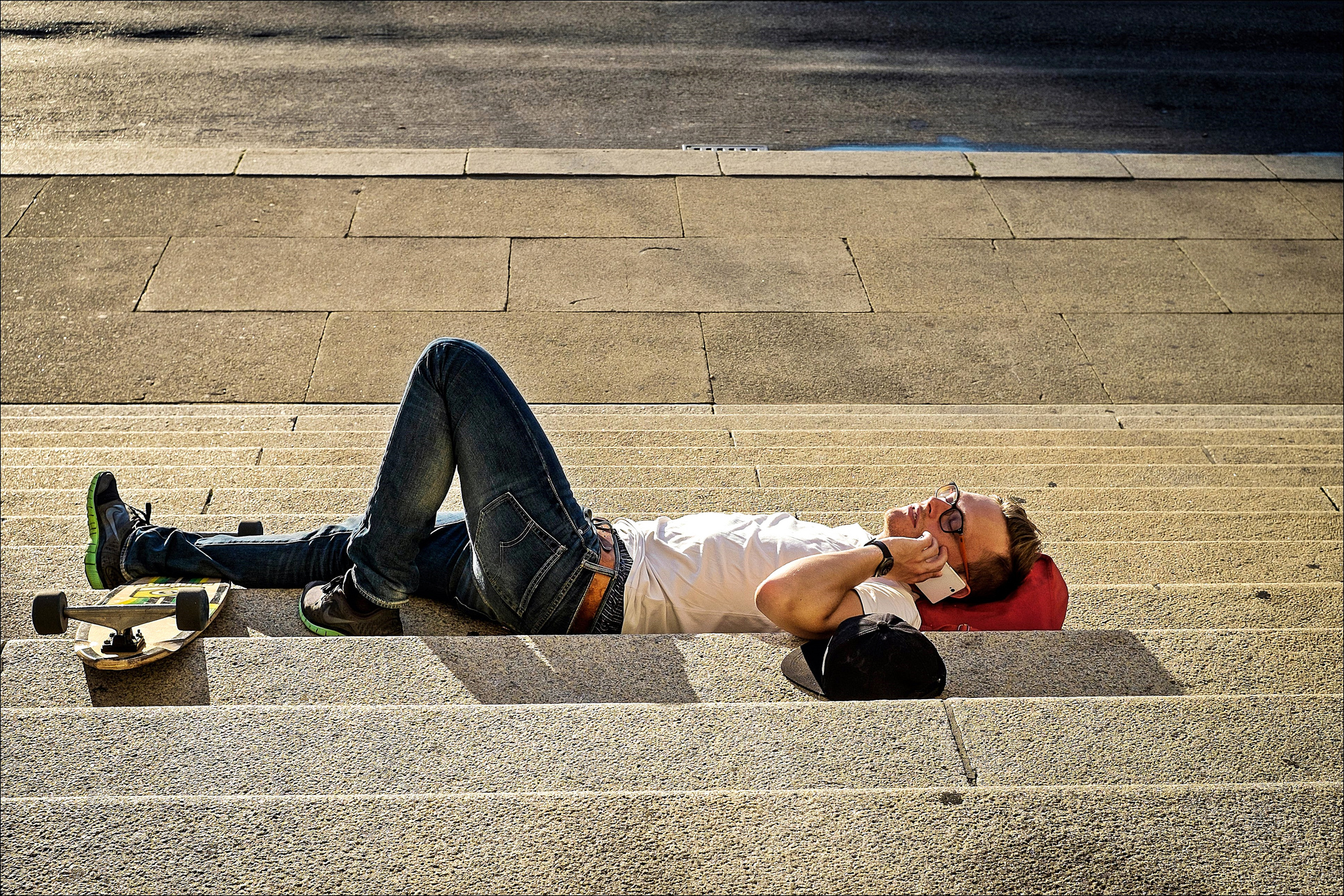 Man lies comfortably on his back in the sun on public steps, his skateboard at this feet, phone in hand.