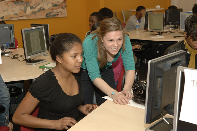 Photo of one woman sitting in front of a computer station in a lab, with another woman leaning over her. Both are smiling and looking at a monitor, with other people at other computers around them