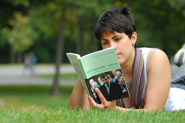 "Photo of woman lying on grass, reading ""How Ottowa Spends 2009-2010"""