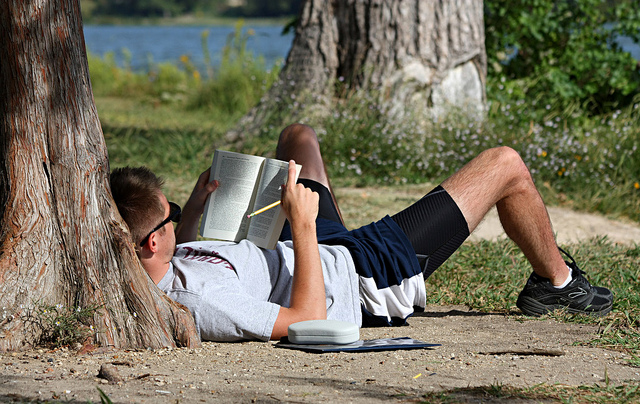 Photo of a man lying on the ground, against a tree, holding a book and a pencil in hand
