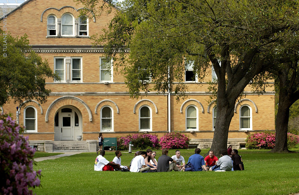 A group of students sits in a circle on the lawn in front of a college building.