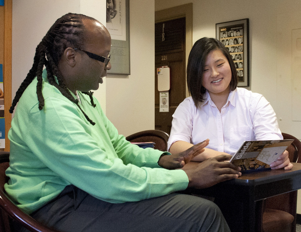 A male college counselor meets with a female student, who looks at a resource pamphlet.