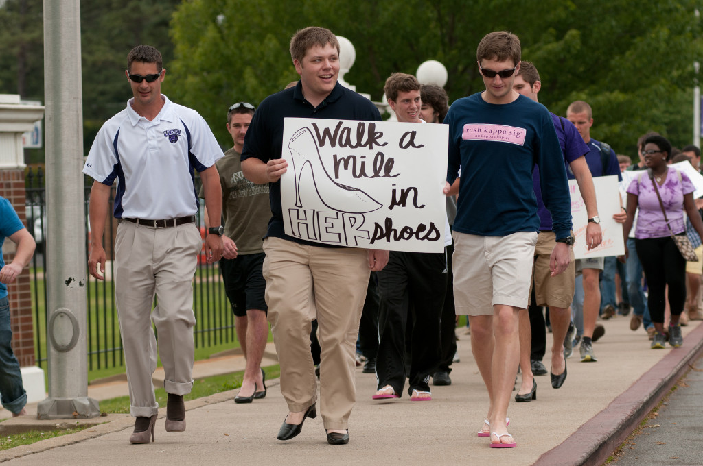 "A group of male students is walking; most are wearing women's shoes, and one holds a sign that reads, ""Walk a Mile in Her Shoes."""