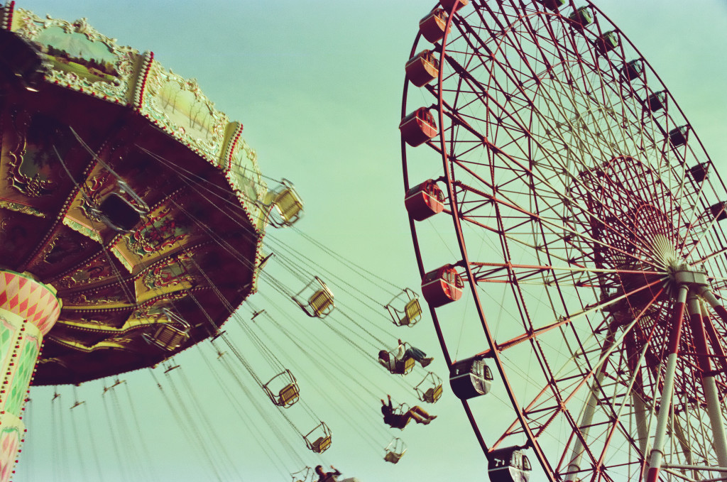 Color photo of a carrousel and a ferris wheel.