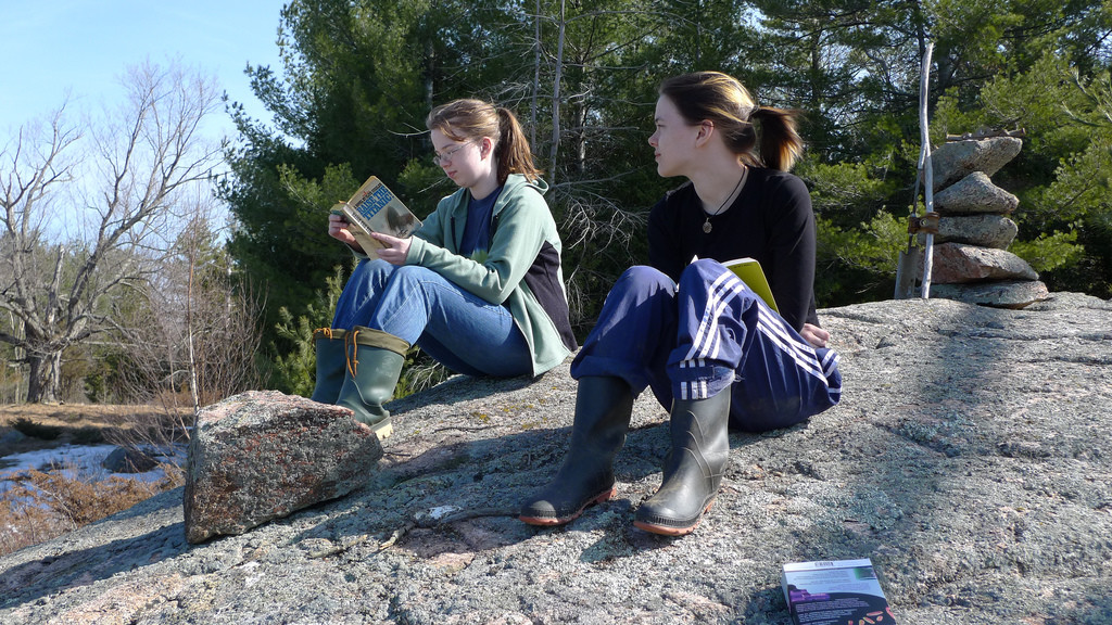 Photo of two young women sitting on a rock. One is reading a book.