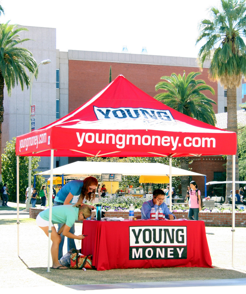 "Photo of bright red ""youngmoney.com"" information tent staffed by several students."