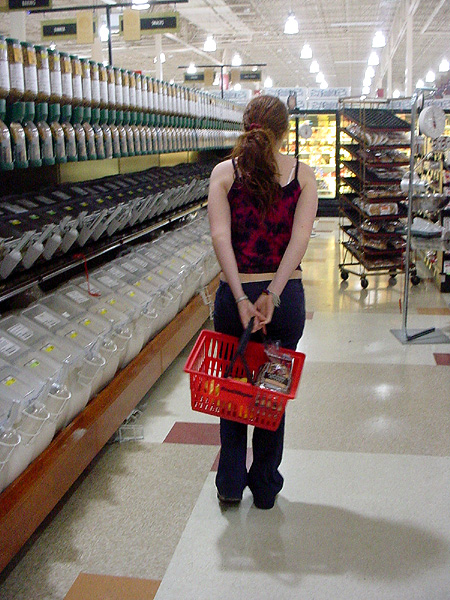 "Photo showing the back of a young woman standing in a supermarket holding a shopping basket staring down a long aisle of ""bulk foods."""
