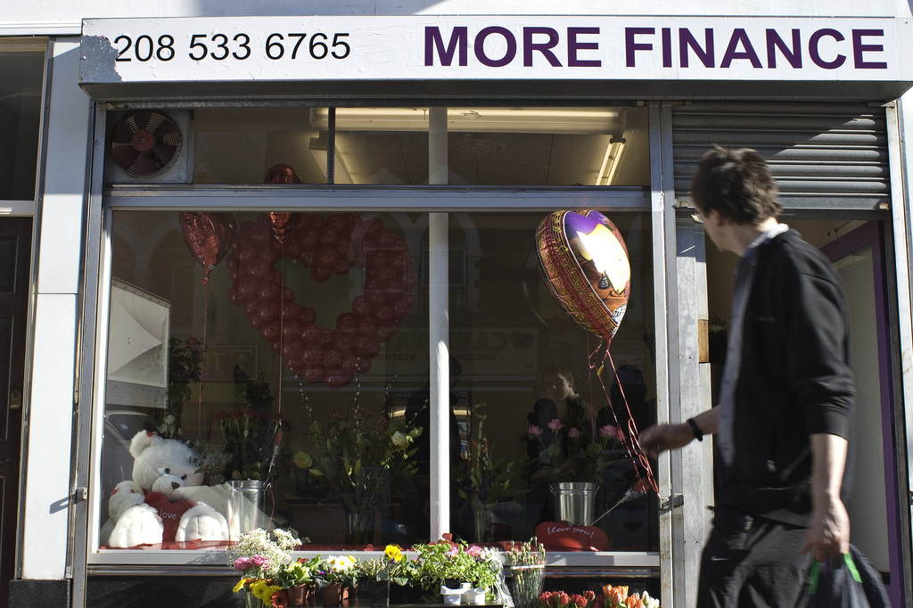 "A young man walks by a shop window. A sign at the top, which has a phone number and reads, ""More Finance,"" apparently catches his eye."