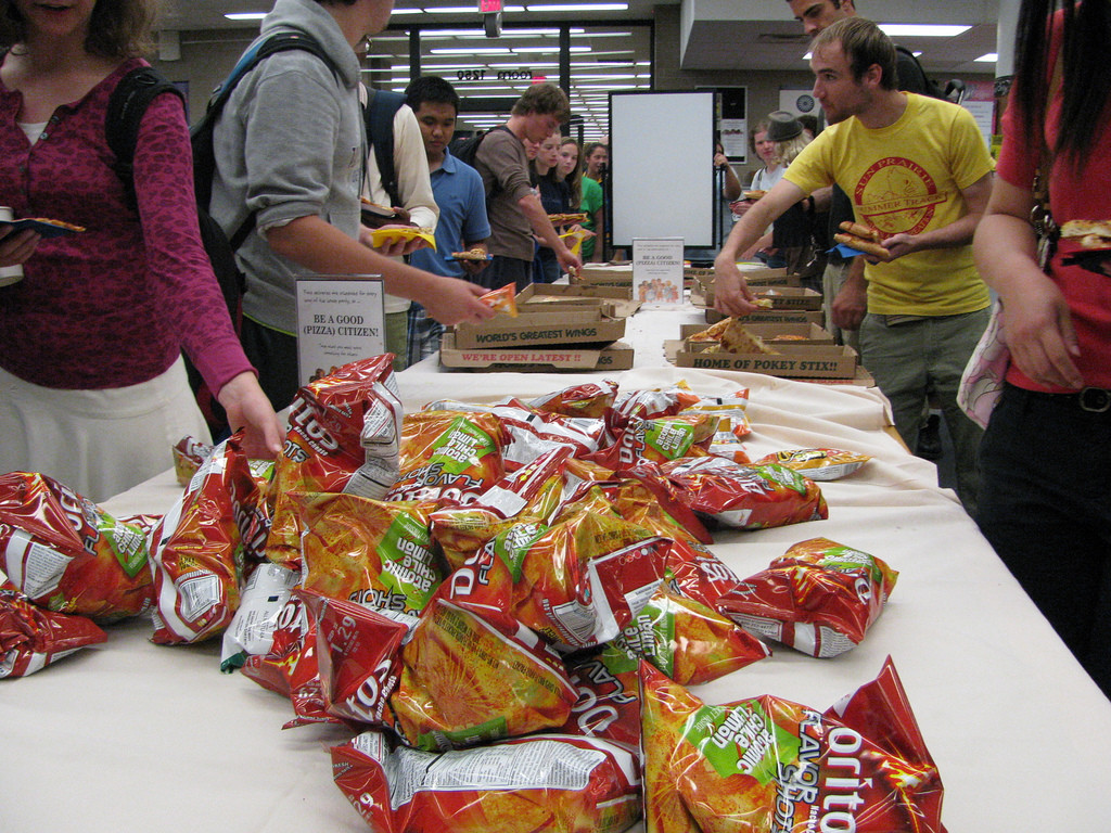 Photo of a college cafeteria. Students push lunch trays past a pile of Doritos and pizza.