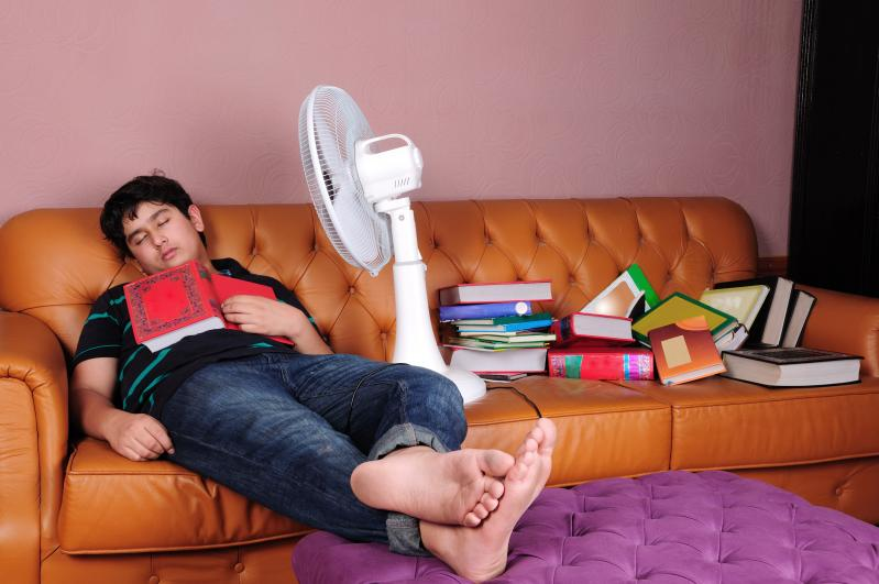 Photo of a male student asleep on a couch amid a pile of book. A fan is aimed at his face, and a book lies open on his chest