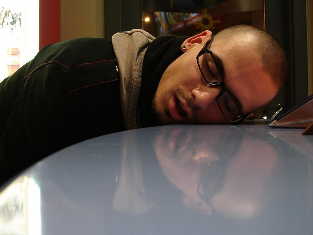 "Photo of a young man asleep or ""passed out."" His eyes are closed and his cheek is resting on the table."