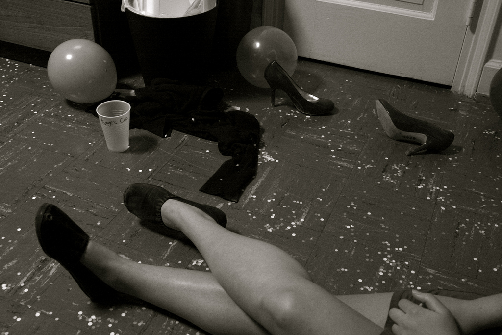 Photo of a woman's legs. Though mostly out of the frame, she appears to be sitting on the floor at a party. Next to her, on the floor, is a pair of high-heeled women's shoes, a party balloon, a plastic beer cup.