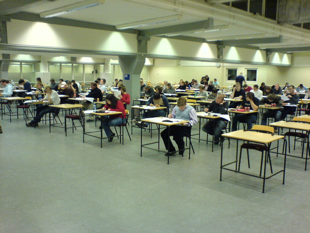 Photo of a room full of students seated at individual desks taking an exam.