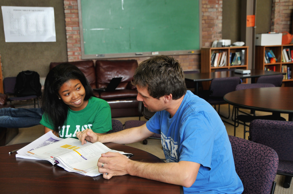 A female student gets help from a male teacher. They're seated at a table in a large classroom, she's smiling, and he's pointing to something in a textbook.