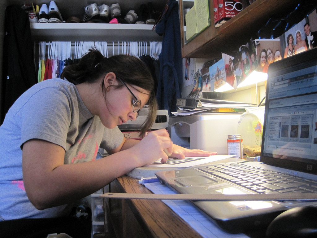 Photo of a young woman focused intently on writing something. She is leaned over her desk; her keyboard and computer are beside her.