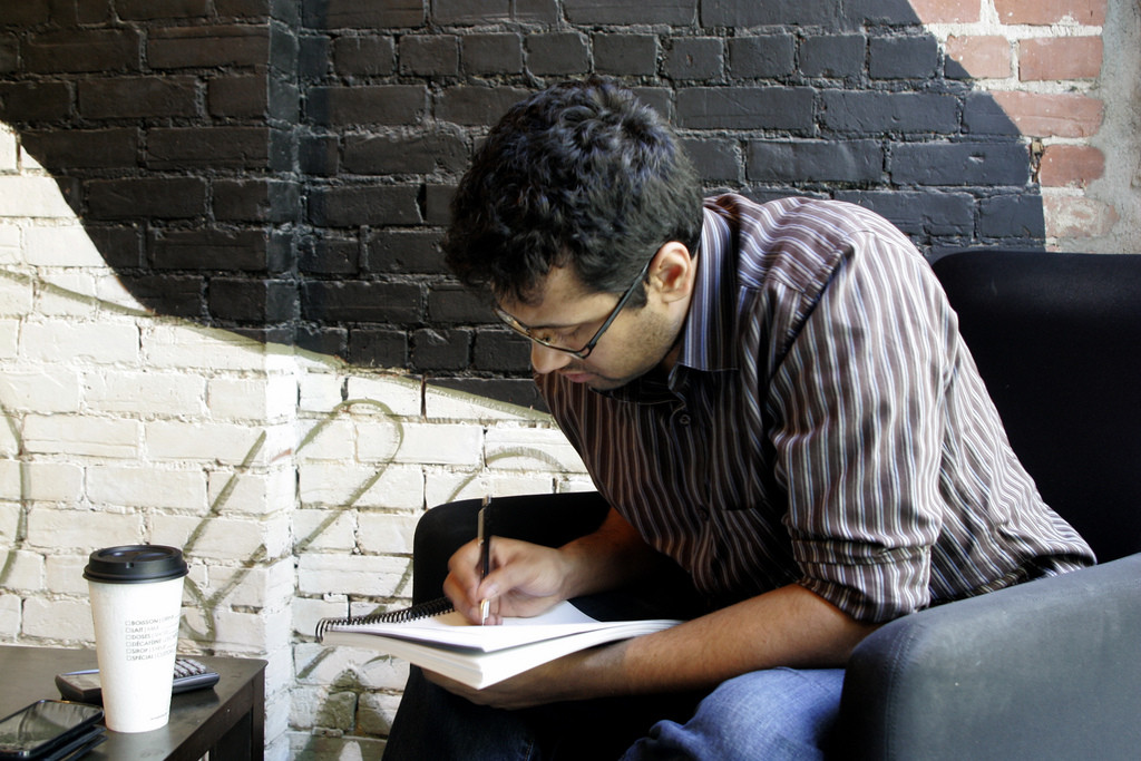Photo of a male student writing in a notebook.