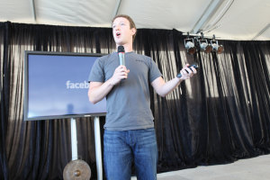 Mark Zuckerberg giving a talk standing in front of a display with the facebook logo