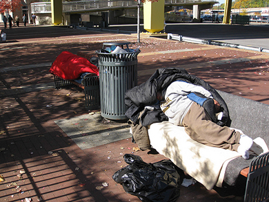 Photo of two homeless people asleep on public city benches