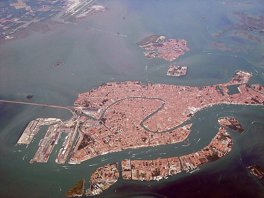 Bird's-eye-view of Venice; there is a road connecting the city on the water to the mainland of Italy.