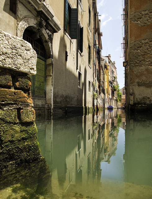 A building can be seen nearly perfectly reflected in the canal; however, the water distorts and discolors the image.