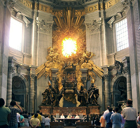 The chair of St. Peter is ornately carved and raised above the congregation and clergy in the church. It is made to larger than life proportions. It is surrounded by gold and wooden representations of clouds, saints, and sunlight. There is a window in the center of the gilding above the chair. The sun is caught in the window.