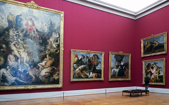 A photograph of 5 paintings, four of them approximately the height of the man who is standing in front of them in the photograph. The fifth is twice the size of the others. The paintings depict various scenes and topics.