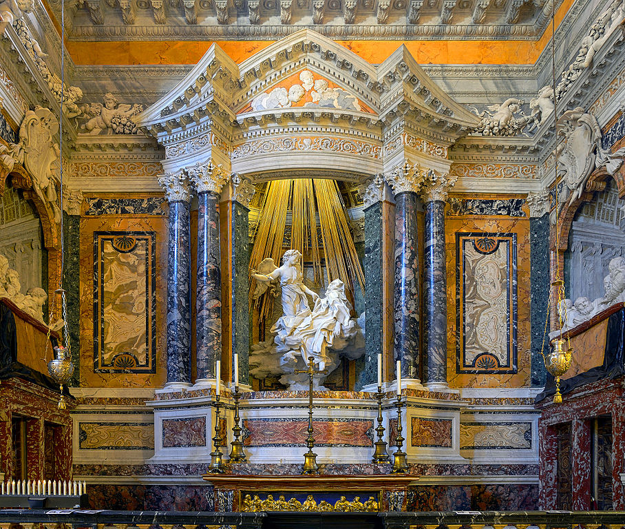 The focus of this work is a sculpture of an angel appearing to Saint Teresa with golden beams descending from the ceiling behind the two figures. The entirety of the walls, however, are a part of the work as well. Corinthian columns frame the sculpture and the walls are made of exquisite marble. We can see two alcoves with carved viewers on either side of the Ecstasy.