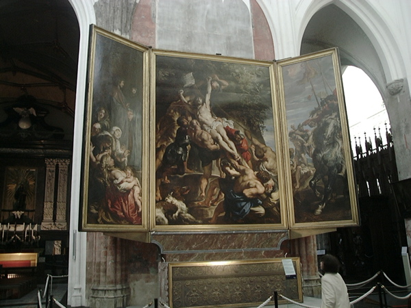A triptych. The central panel shows Christ being raised on the cross. The left panel shows Christ's followers, including Saint John and The Virgin Mary mourning. The right panel shows Roman soldiers on horseback.