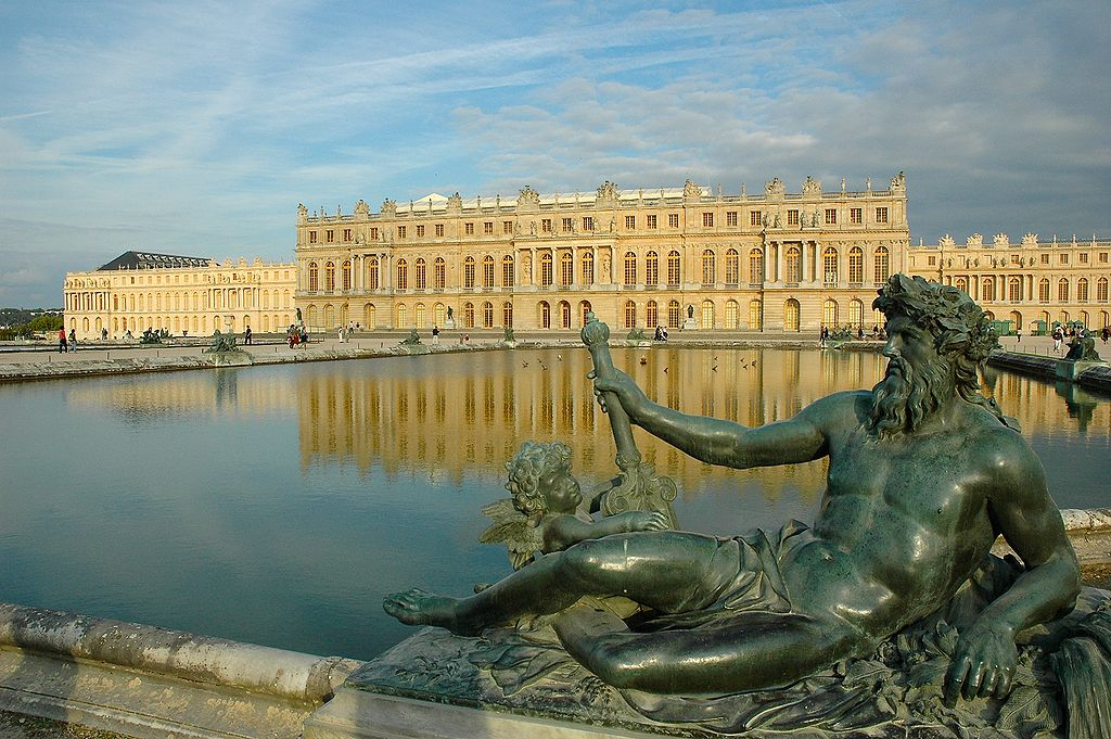 A statue lounges at the edge of a large artificial moat. On the far side of the water is the palace Versailles. The building is expansive, with two different songs visible from this side.